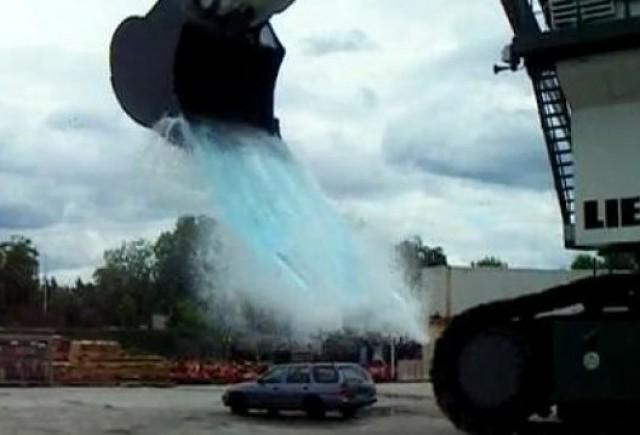VIDEO: Un excavator urias varsa 43 de tone de apa pe o masina